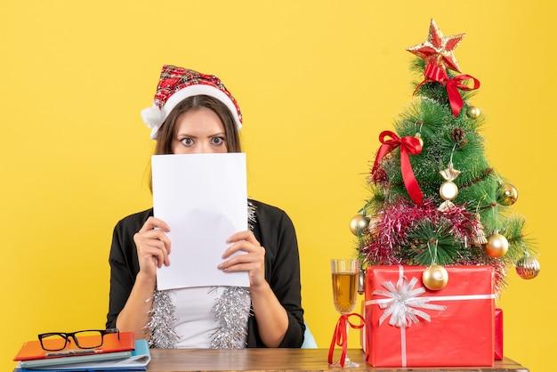 Mulher de negócios chocada, de terno com chapéu de papai noel e decorações de ano novo, trabalhando sozinha e sentada em uma mesa com uma árvore de natal no escritório