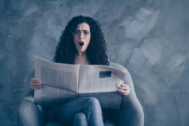 Mulher de negócios chocada e preocupada, sentada na cadeira, lendo um resumo das notícias isoladas sobre a parede cinza