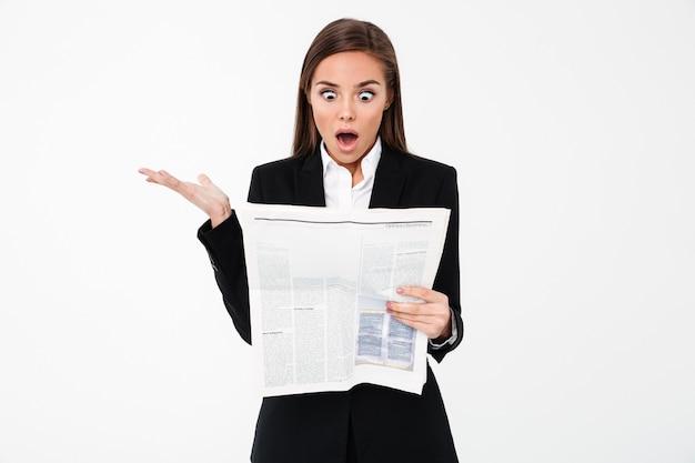 Mulher de negócios chocado segurando o jornal.