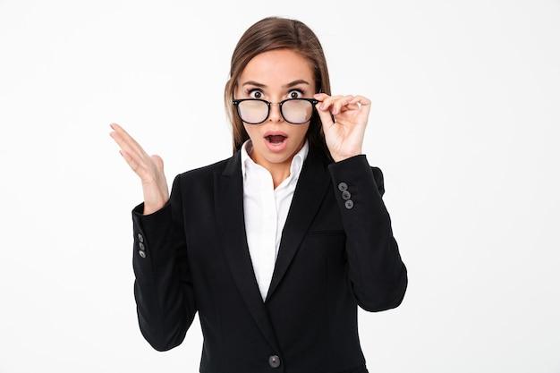 Mulher de negócios chocado usando óculos em pé isolado