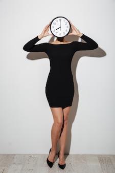 Mulher de negócios cobrindo o rosto com o relógio.