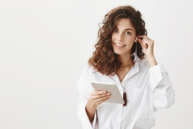 Mulher de negócios coloca fone de ouvido sem fio e segura tablet digital, sorrindo