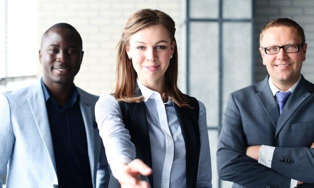 Mulher de negócios com a mão aberta pronta para um aperto de mão no escritório.