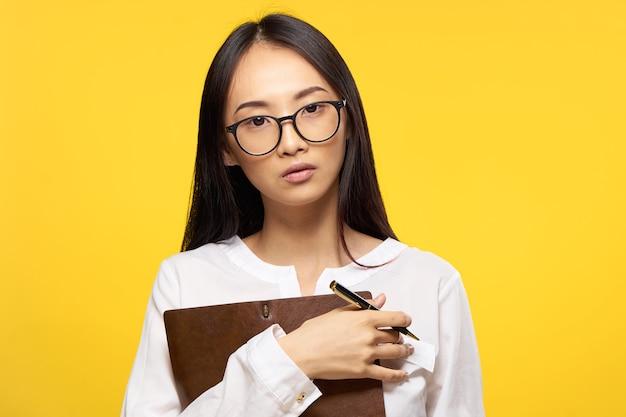 Mulher de negócios com as mãos do caderno e o fundo amarelo do gerente do escritório da caneta. foto de alta qualidade