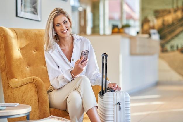 Mulher de negócios com bagagem no saguão de um hotel moderno usando smartphone