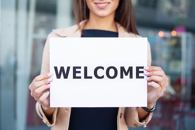 Mulher de negócios com cabelo comprido, segurando uma placa de sinal com um bem-vindo tem aeroporto
