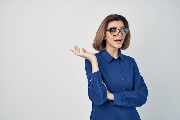 Mulher de negócios com camisa azul e óculos de glamour, posando de fundo claro.