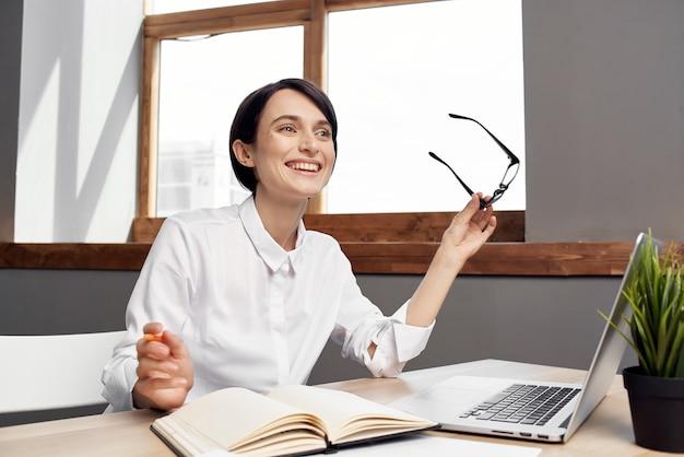 Mulher de negócios com camisa branca na mesa de trabalho na frente da tecnologia do laptop
