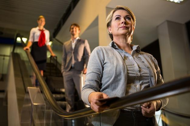 Mulher de negócios com cartão de embarque na escada rolante