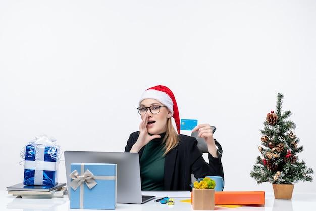 Mulher de negócios com chapéu de papai noel e usando óculos, sentada à mesa segurando um cartão de banco e ligando para alguém no escritório