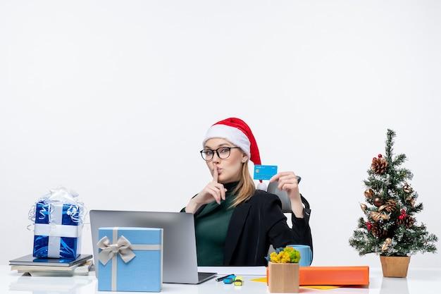 Mulher de negócios com chapéu de papai noel e usando óculos, sentada à mesa segurando um presente de natal e cartão do banco, fazendo gesto de silêncio no escritório