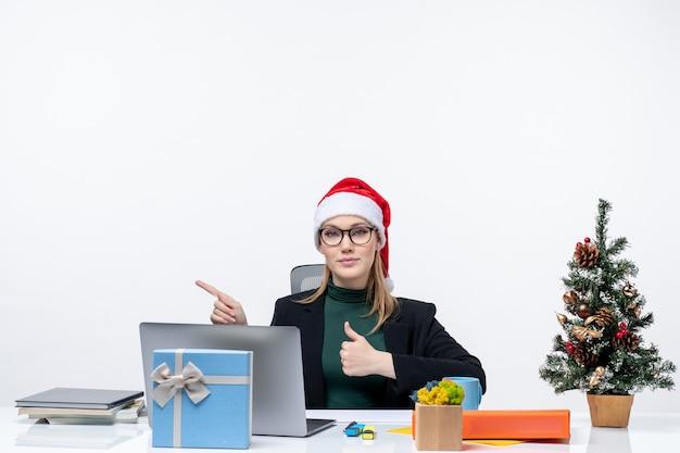 Mulher de negócios com chapéu de papai noel sentada à mesa com uma árvore de natal e um presente