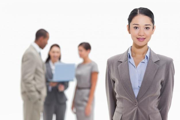 Mulher de negócios com colegas de trabalho assistindo um laptop no fundo