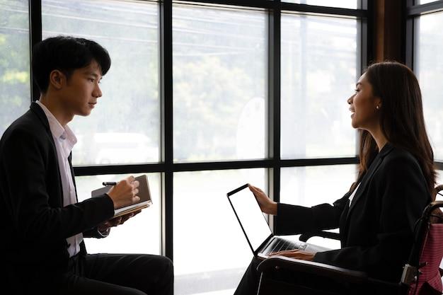 Mulher de negócios com deficiência em cadeira de rodas, sentada em um escritório moderno e trabalhando com seus colegas.