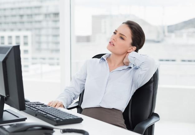 Mulher de negócios com dor no pescoço sentado na mesa