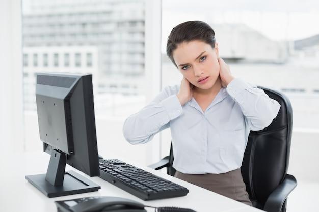 Mulher de negócios com dor no pescoço sentado no escritório
