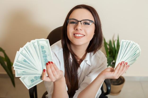 Mulher de negócios com fãs de dinheiro nas mãos