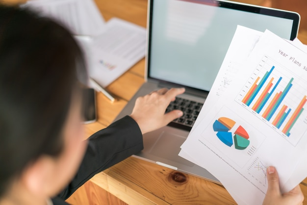 Mulher de negócios com gráficos financeiros e laptop na mesa.