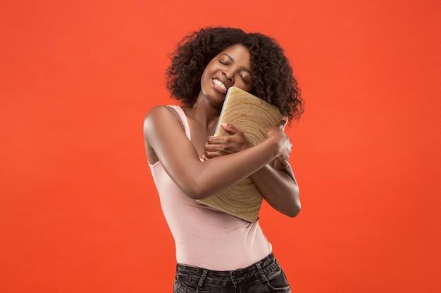 Mulher de negócios com laptop. amo o conceito de computador. retrato frontal feminino atraente com metade do comprimento, moderno estúdio vermelho backgroud. jovem mulher afro emocional. emoções humanas, conceito de expressão facial.