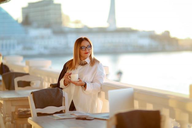 Mulher de negócios com laptop em mulher adulta com óculos e uma xícara de café ou laptop na mão