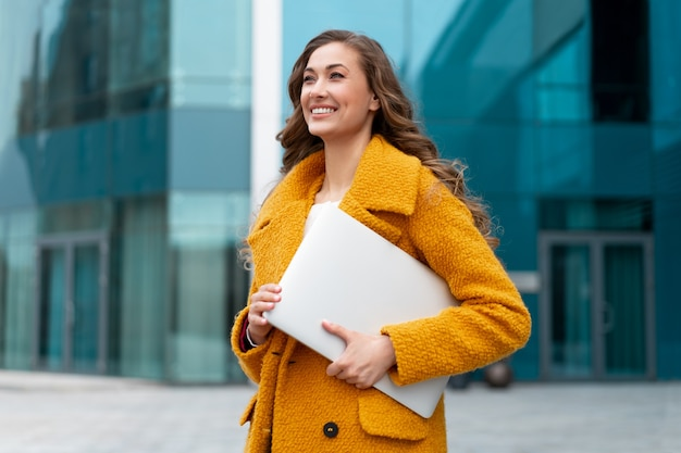 Mulher de negócios com laptop vestida de casaco amarelo em pé ao ar livre fundo de edifício corporativo mulher de negócios caucasiana na rua perto de prédio de escritórios mulher de negócios elegante