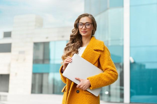 Mulher de negócios com laptop vestida de casaco amarelo em pé ao ar livre fundo de edifício corporativo óculos de pessoa de negócios do sexo feminino caucasiano na rua perto de prédio de escritórios mulher de negócios elegante