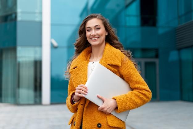 Mulher de negócios com laptop vestido de casaco amarelo em pé ao ar livre superfície do edifício corporativo mulher de negócios branca na rua perto do prédio de escritórios mulher de negócios elegante