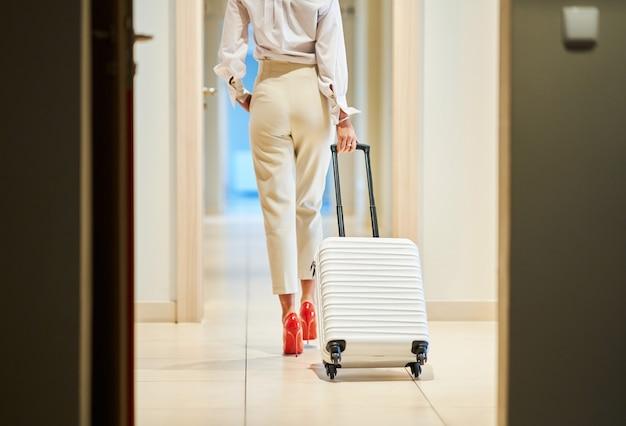 Mulher de negócios com mala branca no saguão de um hotel moderno