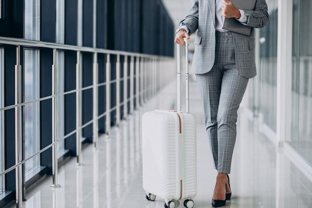 Mulher de negócios com malas de viagem no aeroporto, segurando laptop