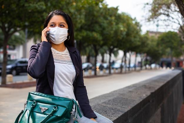 Mulher de negócios com máscara, ela está sentada falando ao telefone