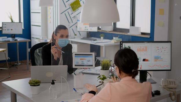 Mulher de negócios com máscara facial analisando estatísticas com seu colega usando um computador tablet digital. equipe trabalhando em um novo escritório normal respeitando a distância social para prevenir a infecção com covid 19