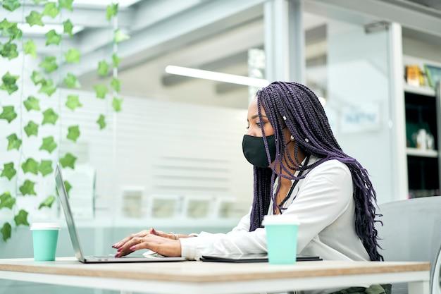 Mulher de negócios com máscara facial sentada na mesa do escritório segurando café