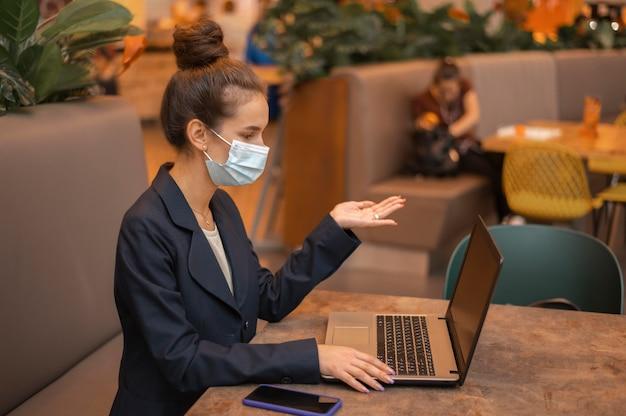 Mulher de negócios com máscara médica trabalhando em seu laptop