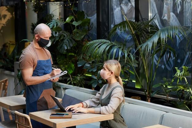 Mulher de negócios com máscara protetora trabalhando na mesa com o laptop e fazendo um pedido ao garçom com máscara. eles estão no restaurante
