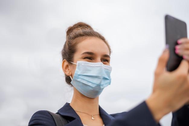 Mulher de negócios com máscara tirando uma foto