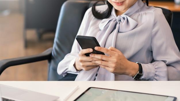 Mulher de negócios com o intervalo e usando o smartphone favorito no escritório.