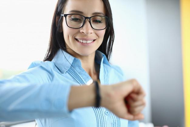 Mulher de negócios com óculos sorri e olha para o relógio