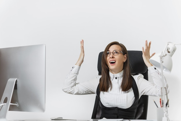 Mulher de negócios com raiva frustrada sentada à mesa, trabalhando no computador com documentos em um escritório leve, xingando e gritando, segurando as mãos para cima, copie o espaço para o anúncio