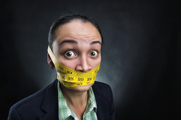 Mulher de negócios com régua de fita em volta do rosto sobre cinza