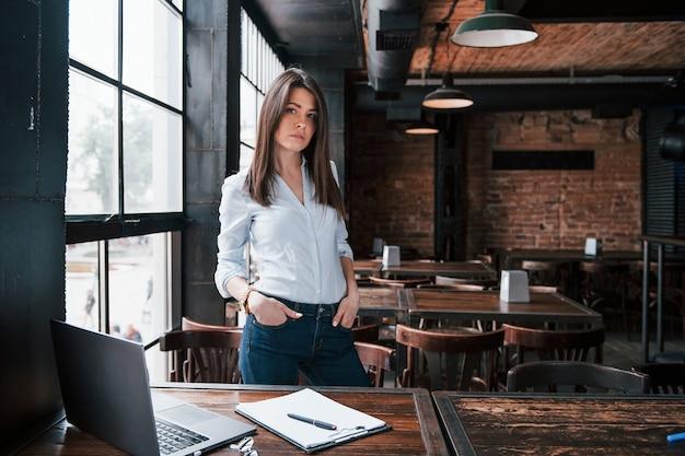 Mulher de negócios com roupa oficial está dentro de casa no café durante o dia.