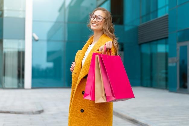 Mulher de negócios com sacolas de compras vestida com casaco amarelo caminhando ao ar livre fundo de edifício corporativo mulher de negócios caucasiana perto de prédio de escritórios venda de temporada elegante empresária