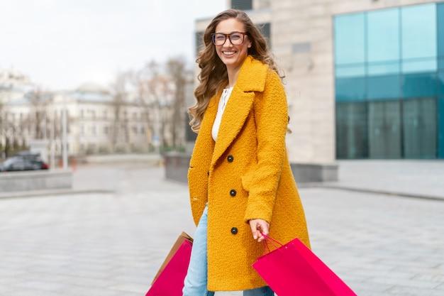 Mulher de negócios com sacolas de compras vestida de casaco amarelo caminhando ao ar livre superfície do edifício corporativo mulher de negócios caucasiano perto de prédio de escritórios venda de temporada elegante empresária