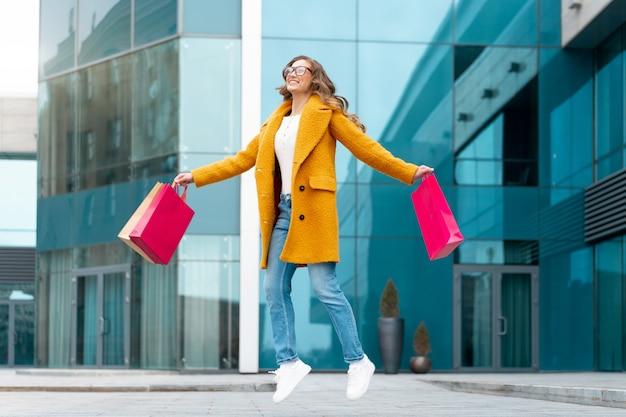 Mulher de negócios com sacolas de compras vestida de casaco amarelo saltar de felicidade ao ar livre edifício corporativo caucasiana mulher de negócios perto de um edifício de escritórios elegante mulher de negócios venda de temporada