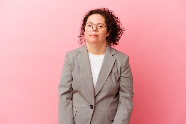 Mulher de negócios com síndrome de down isolada em fundo rosa encolhe os ombros e abre os olhos confusos.