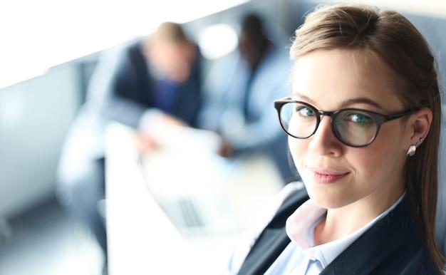 Mulher de negócios com sua equipe, grupo de pessoas no fundo de um escritório moderno e luminoso dentro de casa