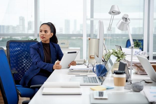 Mulher de negócios com tablet digital sentada na mesa do escritório com computador tablet e olhando para longe