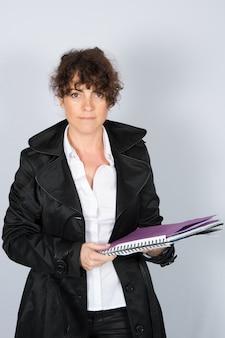 Mulher de negócios com um casaco está trabalhando segurando um caderno