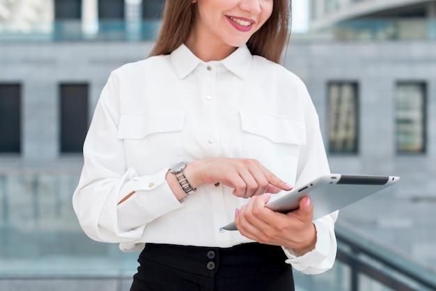 Mulher de negócios com um tablet na rua