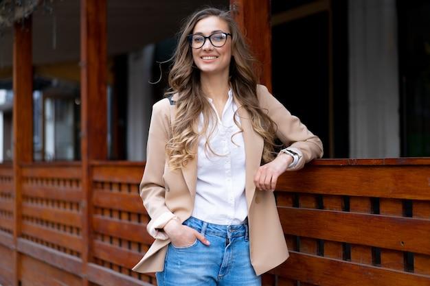 Mulher de negócios com um terno elegante vestido de dona de restaurante em pé perto de um restaurante ao ar livre. caucasiana mulher óculos homem de negócios