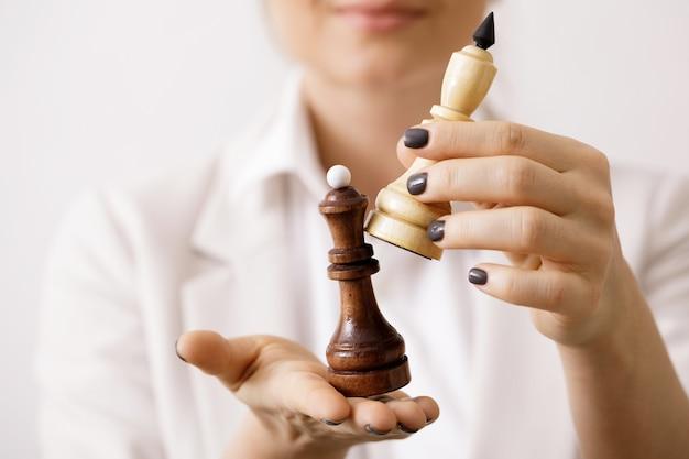 Mulher de negócios com uma figura de xadrez nas mãos. movimentos inteligentes e estratégia nos negócios.